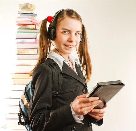 Teen girl with electronic book with a stack of printed books behind Stock Photo - 10325882