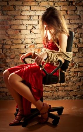 gefesselt: Frau gefesselt mit einem Seil gegen die Wand