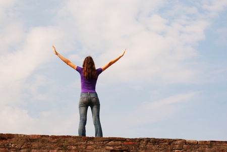 christian youth: Young woman staying with raised hands against blue sky