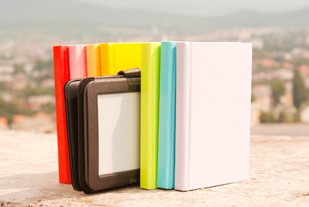 Row of colorful books with electronic book reader photo