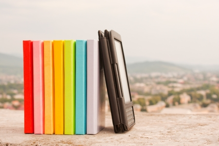 ebook: Row of colorful books with electronic book reader Stock Photo