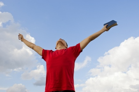 Young man staying with raised hands against blue sky Stockfoto