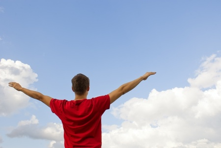 Young man staying with raised hands against blue sky Stock Photo - 10345998