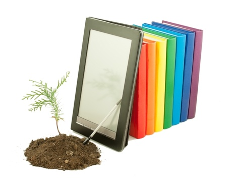 Tree seedling with row of books and electronic book reader behind isolated on white photo