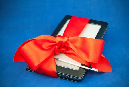 stilus: Electronic book reader tied up with red ribbon