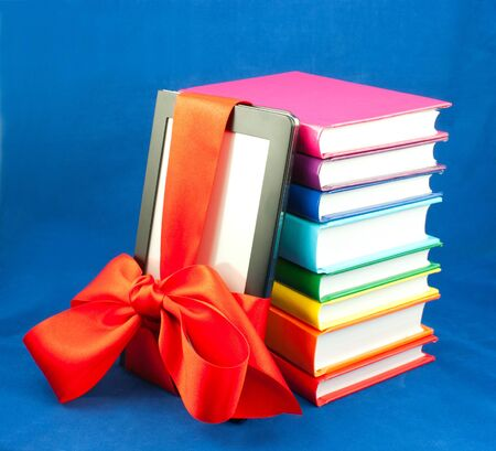 Electronic book reader tied up with red ribbon and stack of books Stock Photo - 10516458