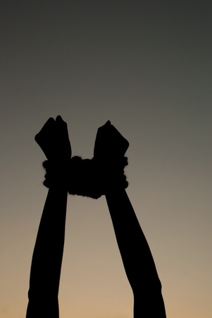 slavery: Hands tied up with rope against dark sky
