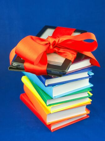 Electronic book reader tied up with red ribbon on the stack of books photo