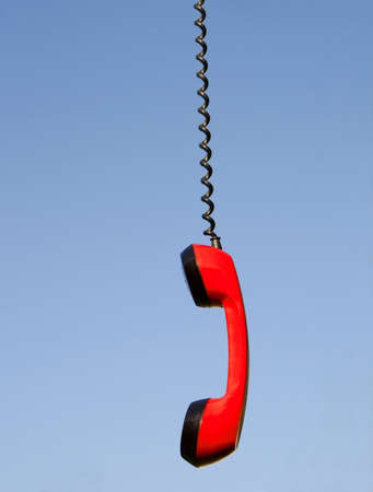 handset: Red phone handset hanging against blue sky Stock Photo