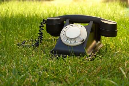 Retro styled rotary telephone in the grass photo