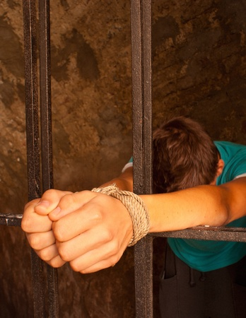 Man with hands tied with rope behind the bars Stock Photo - 10879305