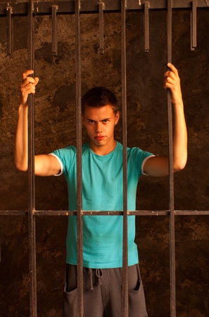 Man with hands tied with rope behind the bars Stock Photo - 10879306