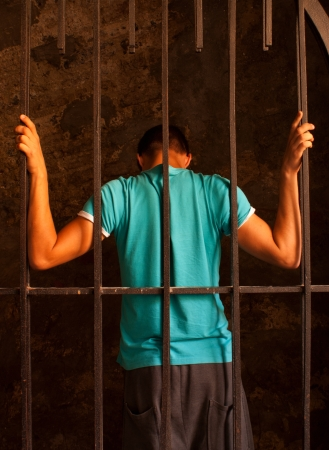 Man with hands tied with rope behind the bars Stock Photo - 10879303