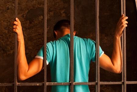 prison cell: Homme avec les mains attach�es avec une corde derri�re les barreaux