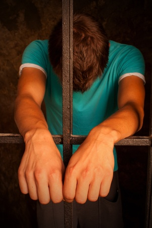 an inmate: Man with hands tied with rope behind the bars
