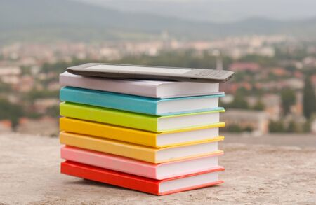 Stack of colorful books with electronic book reader photo