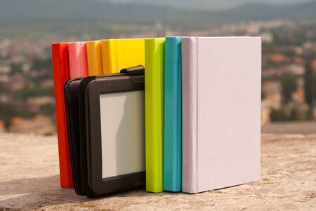 Row of colorful books with electronic book reader Stock Photo - 10879310