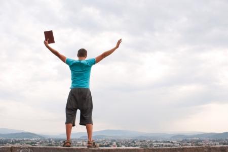 manos levantadas al cielo: Joven permanecer con las manos alzadas contra el cielo azul