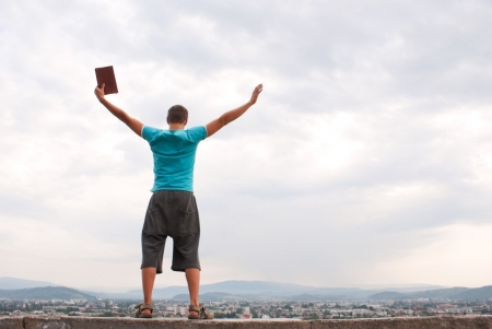 man praying: Young man staying with raised hands against blue sky Stock Photo