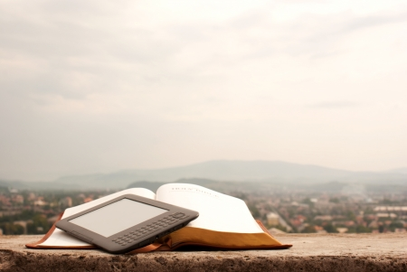 readers: Electronic book reader laying on the book outdoors