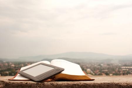 leer biblia: Lector de libros electr�nicos que pone en el libro al aire libre