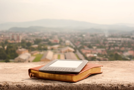 Electronic book reader laying on the book outdoors Stock Photo - 10915545