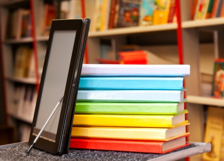 e store: Stack of colorful books with electronic book reader