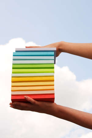 Hands holding colorful hard cover books