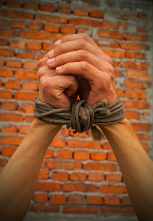 Hands tied up with rope against brick wall Foto de archivo