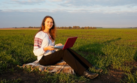 Young lady sitting outdoors with a laptop Stock Photo - 11028649