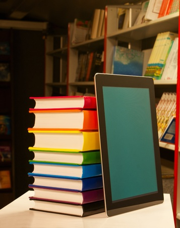 Stack of colorful books and electronic book reader in the book shop photo