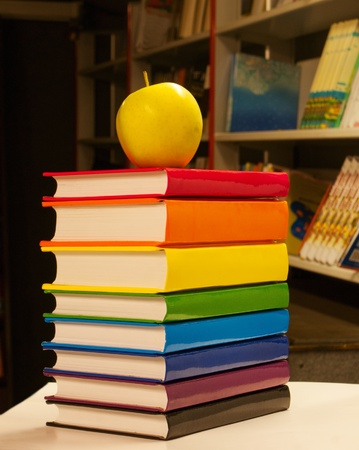 Pile of colorful books with an apple on it photo