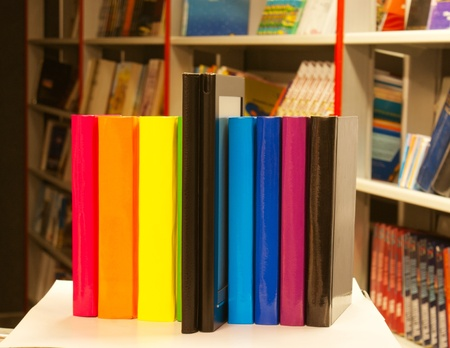 Row of colorful books and electronic book reader in the book shop photo
