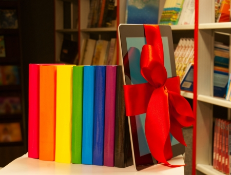 Electronic book reader tied up with red ribbon and row of books photo