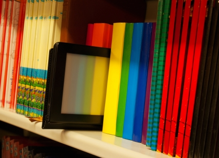 book shelf: Row of colorful books and electronic book reader on the shelf Stock Photo
