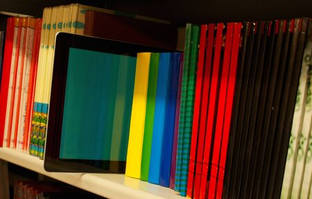 Row of colorful books and electronic book reader on the shelf photo