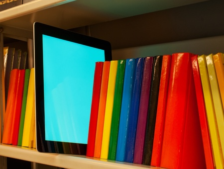 Row of colorful books and electronic book reader on the shelf Stock Photo