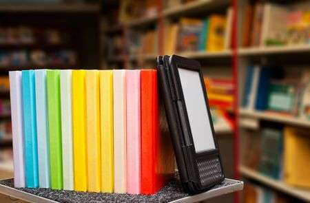 digitized: Row of colorful books with electronic book reader Stock Photo