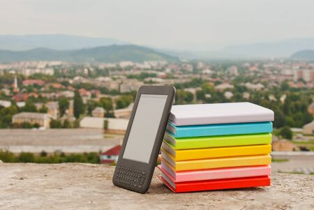 Stack of colorful books with electronic book reader Stock Photo - 11369884
