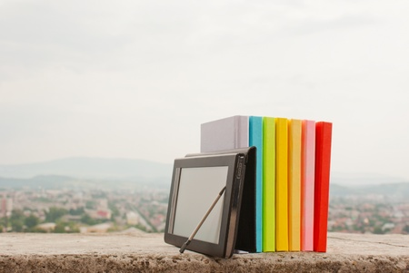 Row of colorful books with electronic book reader Stock Photo