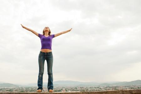 푸른 하늘을 제기 손으로 체류하는 젊은 여자