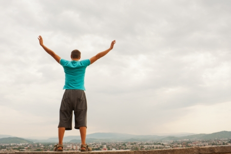 Young man staying with raised hands against blue sky photo