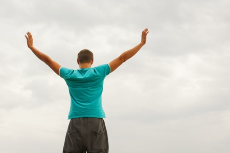 Young man staying with raised hands against blue sky Stock Photo - 11370058