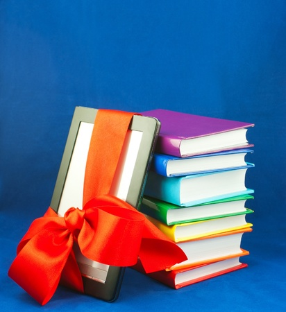 Electronic book reader tied up with red ribbon with stack of books photo