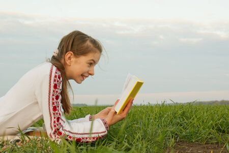 Teen girl reading a book at a field photo