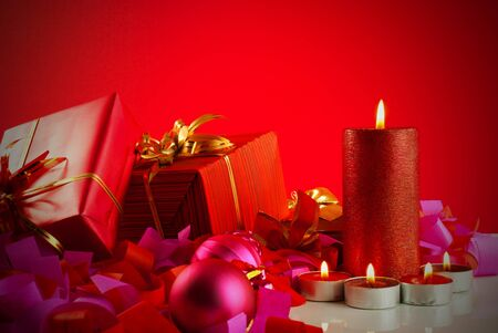 Christmas gifts and candles over red background 写真素材