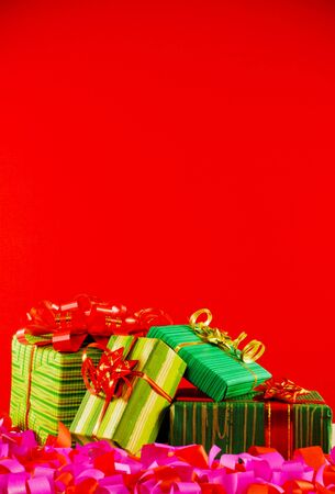 Wrapped boxes with presents against red background photo