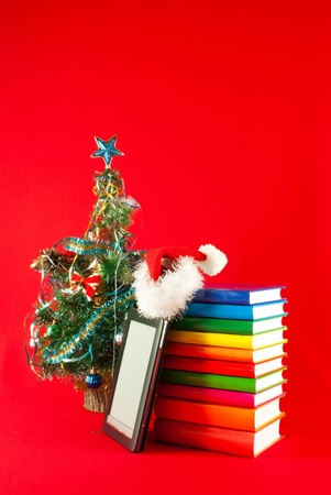 Electronic book reader with stack of books against red background Stock Photo - 11593251