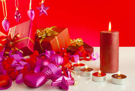 Christmas gifts with candles over red background