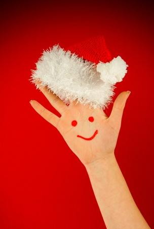 산타의 모자를 쓰고 그것에 인간의 손바닥을 미소 짓는다.